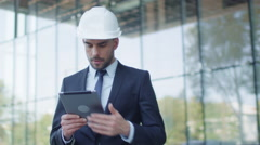 Businessman in Hard Hat Walking, Talking, and Using Tablet Computer. Stock Footage