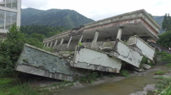 Walking past collapsed buildings of school at earthquake memorial site China Stock Footage