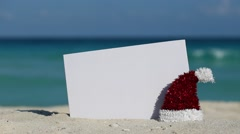 Santa Claus Hat and white blank placard at sandy beach Stock Footage