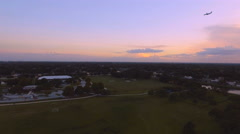 Aerial shot over Town at Sunset with Airplane flying through Sky Arkistovideo