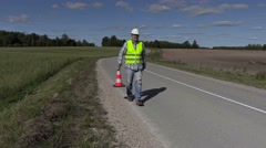 Road construction worker with traffic cone ask where put first cone Stock Footage