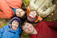 View from above of four smiling people lying on the land Stock Photos