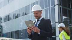 Businessman wearing Hard Hat and Using Tablet Computer on Construction Site. Stock Footage