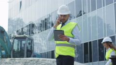Engineer in Hard Hat Talking on the Phone, Holding Tablet Computer in his Hand.  Stock Footage