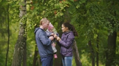 Happy family: Father, Mother and child - little girl in autumn park: dad, mammy Stock Footage