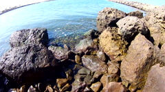 Tranquil waves gently lapping over over harbor rocks. Stock Footage