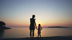 Family, mother and daughter holding hands and walking on a pier at sunset. 4K Stock Footage