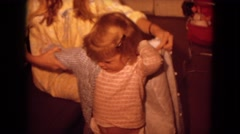 1970: woman putting on clothes on a pouty child who cannot put it on herself, Stock Footage