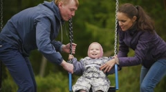 Young happy family at playground - dad, mother and baby daughter - children's Stock Footage