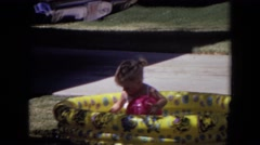 1970: a little girl playing with a red ball as she sits in a yellow kiddie pool Stock Footage