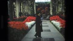 1972: a woman walking through a beautiful arboretum lined with colorful flowers Stock Footage