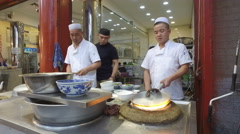 Open kitchen, chefs prepare dishes in popular Muslim restaurant Xi'an, China Stock Footage