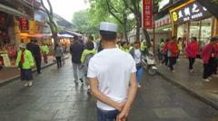 Following a Muslim man walking through a fast changing street in Xian, China Stock Footage