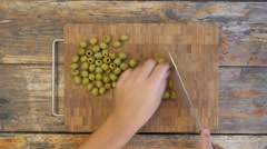 Slicing olives on a rustic wooden table - top view 4K Stock Footage