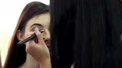 Makeup artist at work with a client in a beauty salon doing make-up Stock Footage
