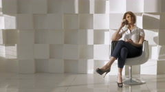 In studio a young girl sitting in a chair and talking on a mobile phone Stock Footage