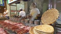 A young man grills lamb kebabs in a popular Muslim quarter in Xian, China Stock Footage