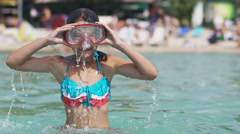 Little girl in underwater mask springs out of sea water. Slow motion 120 fps Stock Footage