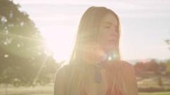 Slow motion pretty girl turns head in sunlight Stock Footage