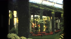 1972: small group of people walking under structure in background of garden area Stock Footage