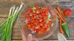 Mixing vegetables of a salad in a glass bowl on a rustic wooden table - flat lay Stock Footage
