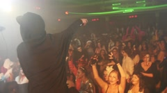 Back side of rap artist perform on stage at Halloween party in crowded club Stock Footage