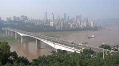 Traffic drives over a bridge across the Yangtze river, Chongqing skyline China Stock Footage