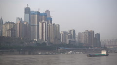 Cargo vessel sails upstream on Yangtze river, construction Chongqing China Stock Footage