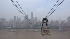 Cable car leaves station, Yangtze river, Chongqing skyline, urban China Stock Footage