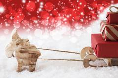 Reindeer With Sled, Copy Space, Red Stars And Bokeh Background Stock Photos