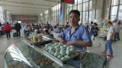 Portrait of vendor selling eggs and breakfast at train station China Stock Footage