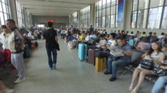 Walking through a waiting hall at the Zhengzhou railway station in China Stock Footage