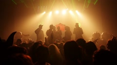Silhouettes people in costumes at stage of crowded nightclub at Halloween party Stock Footage