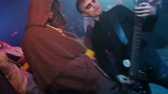Guitarist with blood tears perform on stage. Halloween party. Man in hood. Crowd Stock Footage