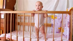 Beautiful happy smiling baby girl standing in bed and looking with interest Stock Footage