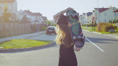 Beautiful and fashion young girl posing with a skateboard Stock Footage