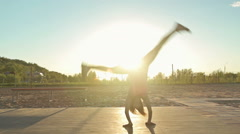 Girl doing cartwheel on a workout Stock Footage