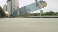 SLOW MOTION CLOSE UP: Young skateboarder jumping and doing tricks on city street Stock Footage