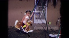 1973: young child riding horse on swingset NEW MEXICO Stock Footage