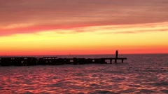 Tilt Down on Sunset Lake and Couple on Jumbled Pier Stock Footage