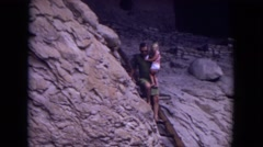 1973: young man and his baby at a place with ruins, climbing down a ladder  Stock Footage