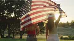 Young woman walking with an American flag flying behind their heads Stock Footage