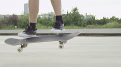 SLOW MOTION CLOSE UP: Skateboarder jumping and doing flip trick on city street Stock Footage