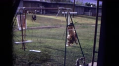 1973: a cute little girl in a western hat swinging on a swing set Stock Footage