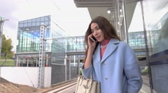 Happy girl in blue coat talking on her mobile phone at train station. 4K shot Stock Footage