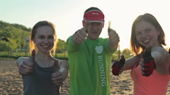 Group of young fitness people show thumbs-up at camera Stock Footage