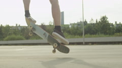 SLOW MOTION CLOSE UP DOF: Skateboarder jumping and doing a flip trick in a city Stock Footage
