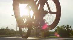 SLOW MOTION CLOSE UP: Bmx biker riding wheelie on back wheel on concrete bench Stock Footage