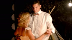 Newlyweds dancing and kissing in a romantic setting with lighter at night Stock Footage