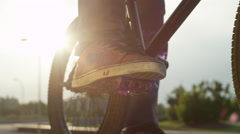 SLOW MOTION CLOSE UP: Bmx biker playing with bike pedal in sunny evening Stock Footage